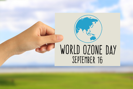 Hand holding a paper card with world ozone day concept on abstract nature background 写真素材