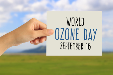 Hand holding a paper card with world ozone day concept on abstract nature background 免版税图像