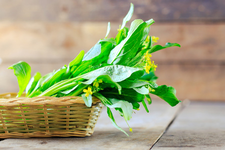 Green choy in basket on wooden table background