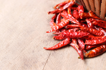 Dried red hot chilli peppers on old wooden table background Stock Photo