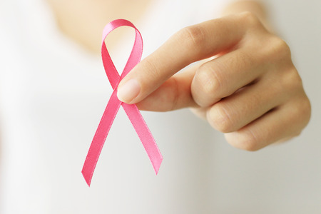 healthcare and medicine concept. Woman hand holding pink cancer awareness ribbon.