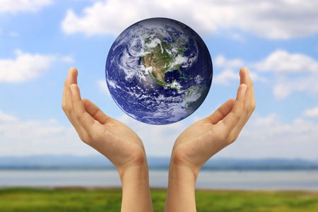 Hand holding the blue Earth. Elements of this image furnished