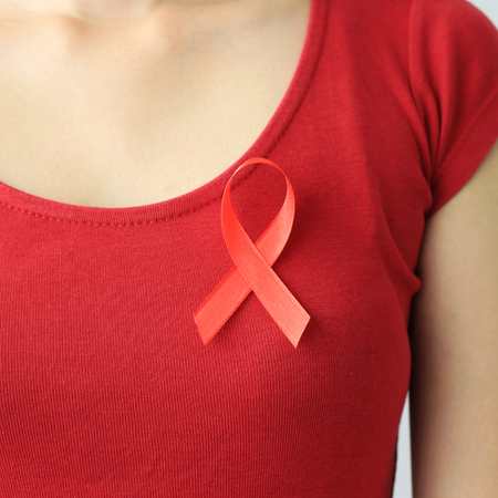 Aids Awareness. female hands holding red AIDS awareness ribbon. Stock Photo
