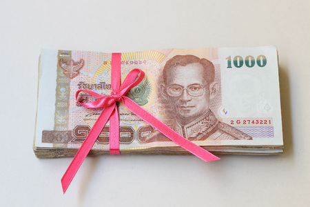 Thai money with pink ribbon