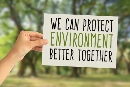Mano sosteniendo una tarjeta de papel con la palabra Podemos proteger mejor el medio ambiente juntos sobre fondo de naturaleza abstracta