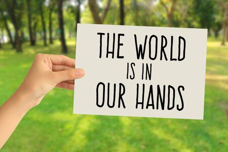 Hand holding a paper card with The world is in our hands word on abstract nature background