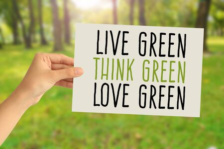 Hand holding a paper card with Live green, Think green, Love green word on abstract nature background Фото со стока