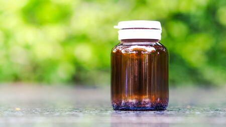 Mock up Medical bottle glass, blurred green background.