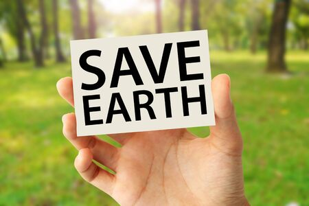 Hand holding a paper card with save earth word on abstract nature background Фото со стока
