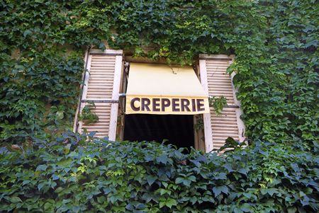 Sign for a French Creperie above a window in a wall grown with ivory Stockfoto