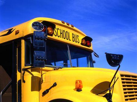Gele schoolbus tegen de blauwe hemel