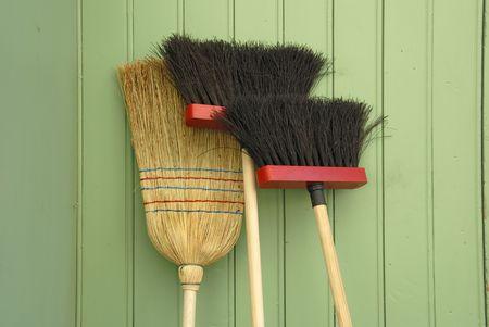Drie bezems tegen groene houten wand