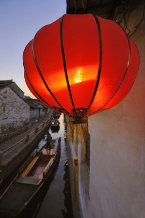 zhouzhuang: View at a canal in Zhou Zhuang CHINA at sunset. At foreground red lampion