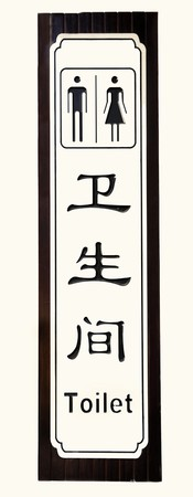 Toilet Sign on wall-- in Chinese and English in black letters and characters. Stock Photo
