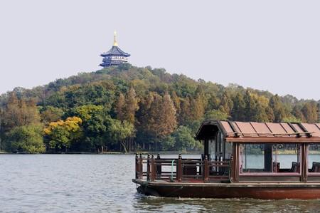 Traditionele boot aan de West Lake (Xihu) in de buurt van Hangzhou in China. Op de achtergrond een pagode