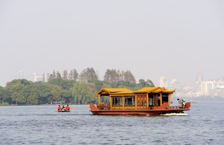 Traditional boat at the West Lake (Xihu)  near Hangzhou in China. At the background the city of Hangzhou.