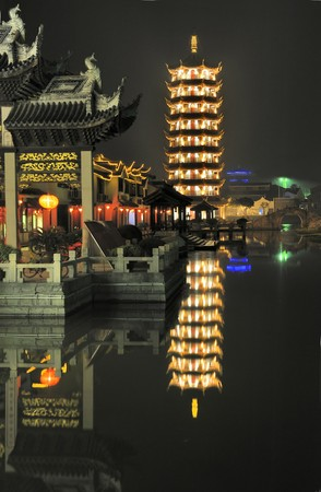 Zhouzhuang, one of the most famous water townships in China, situated in Kunshan City which is only 30 kilometers (18 miles) southeast of Suzhou. Evening in the village Zhouzhuang with illuminated Pagoda at waterside