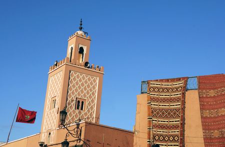 prayer rug: Moroccan Carpets for sale at a shop and minaret of a mosque with Moroccan national flag in Marrakesh Stock Photo