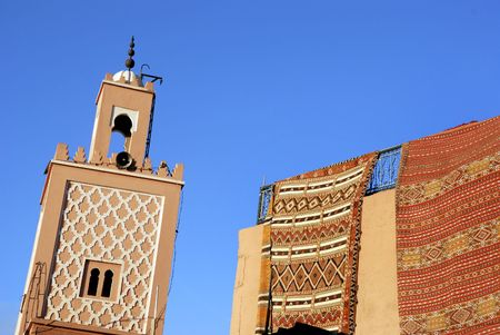 prayer rug: Moroccan Carpets for sale at a shop and minaret of a mosque in Marrakesh