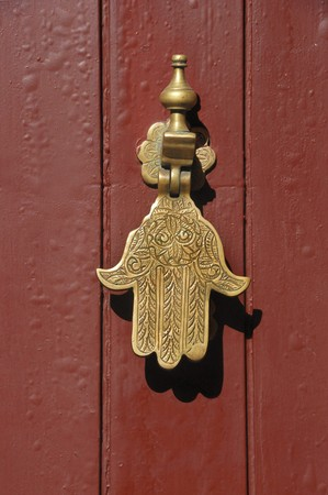 Old knocker in the shape of a hand on a door of a traditional Moroccan house in Marrakesh, Morocco.