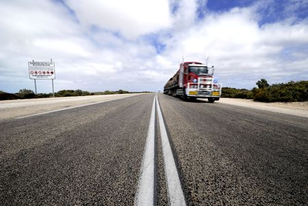 restrictions: Roadtrain in Nullarbor desert,Australia. At left side sign with quarantine restrictions.