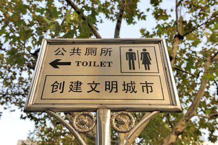 Sign, in Chinese and English in black letters and characters, indicating the way to the public rest rooms
