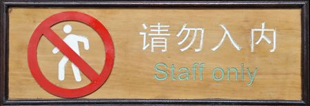 ideogram: Sign on wall-- in Chinese and English in withe and green letters and characters.Entrance  Staff only  Stock Photo