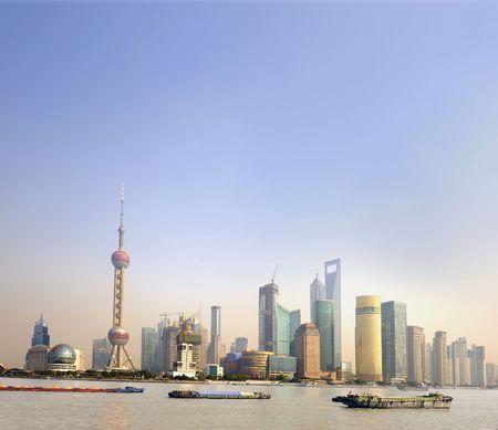 Schepen bij zons ondergang op de Huangpu rivier in Shanghai, China. Op de achtergrond de financiële wijk met wolkenkrabbers en de Pearl Tower.