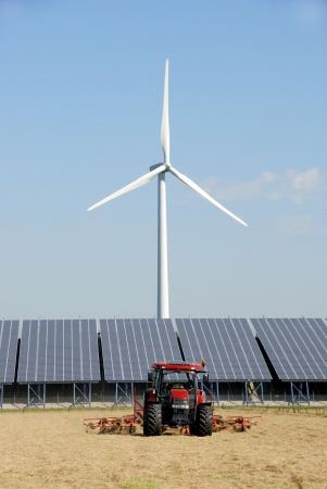 Zonne-installatie met windturbine op een boerderij in de Netherlands.In voorkant twee tractoren