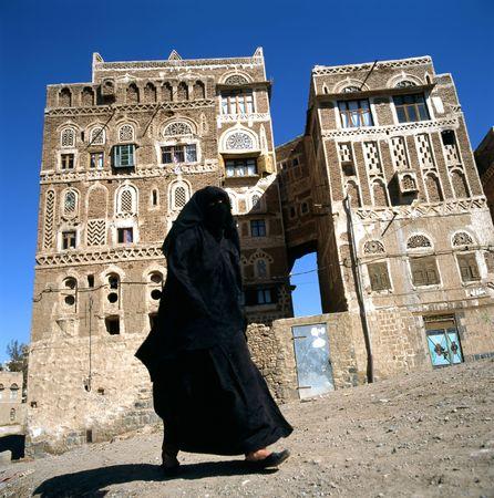 Een Gesluierde islamitische vrouw loopt op een straat van Sanaa, Yemen.At achtergrond typische Jemen huizen.  Stockfoto