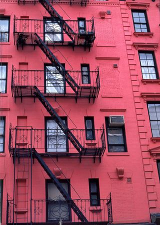 Fire escapes run diagonally down colorful apartment buildings in Greenwich Village, NYC