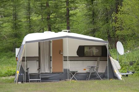 Caravan met satelliet schotel op camping zonder mensen  Stockfoto