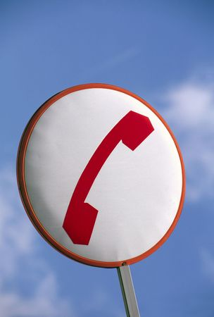 Telephone sign in red and white against a blue sky photo