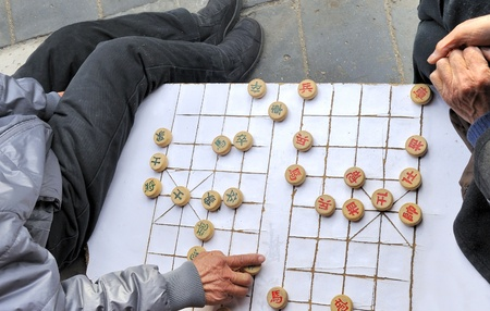 played: A man makes a move on a on a local Beijing Chinese chess game board. Xiangqi, also known as Chinese chess, is an ancient board game played all over the world.