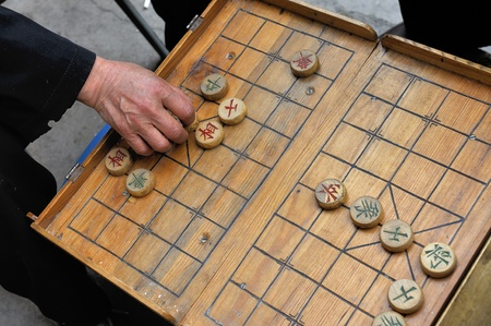 A man makes a move on a on a local Beijing Chinese chess game board. xiangqi, also known as Chinese chess, is an ancient board game played all over the world. photo
