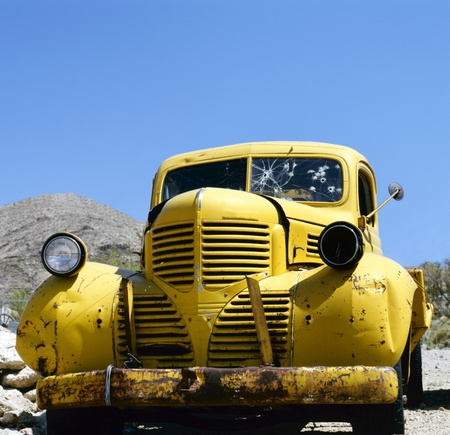 bonnie: An yellow abandoned vehicle Bonnie and Clyde style.Against a clear blue sky