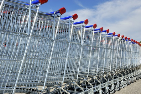 push cart: Shopping carts in a row against blue sky