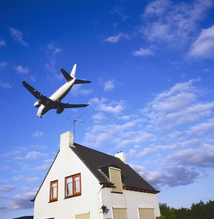 contaminacion acustica: grandes aeronaves de reacci�n en la aproximaci�n para el aterrizaje sobre la vivienda suburbana Foto de archivo