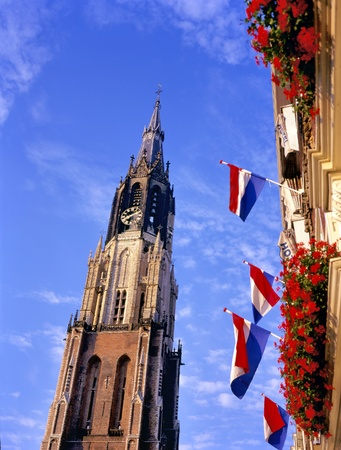 burried: New church and flags at the market place in Delft.In this church the Dutch Royal family is burried.