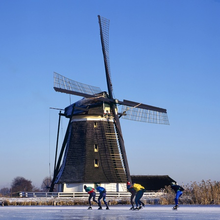 Windmill and skaters at the foreground at a Dutch frozen river photo