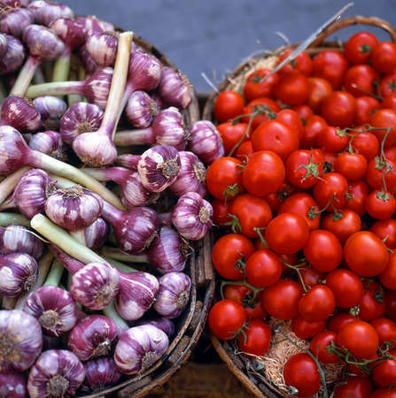 Fresh tomatoes and onions in baskets at a greengrocer photo