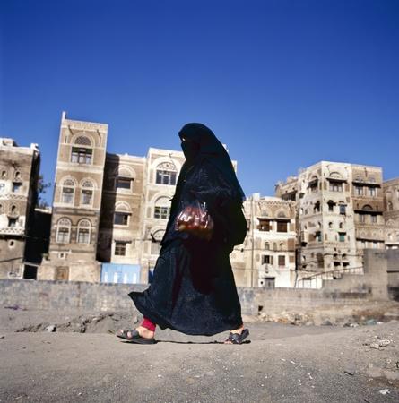 Gesluierde islamitische vrouw loopt op straat Sanaa, Jemen. Op de achtergrond typische Jemen huizen. Stockfoto