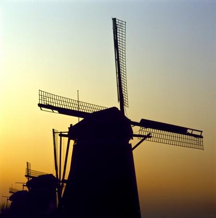 leidschendam: Sunrise behind a group of traditional Dutch windmills on a cold winter morning; Leidschendam, Netherlands