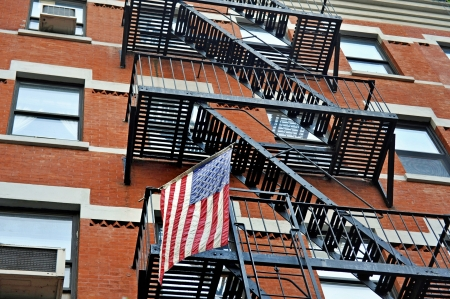 Fire escape stairs outside a New York apartment building with the American national flag photo