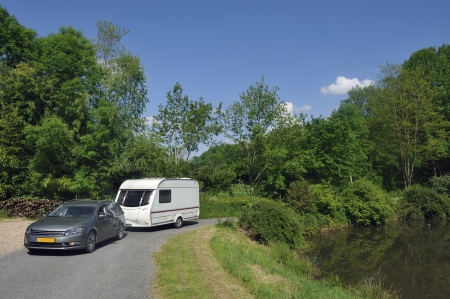 Caravan passing a small lake at a campsite in France