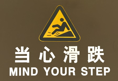 slither: Warning sign in Chinese and English Text is  Mind your step Stock Photo