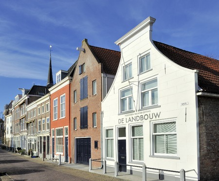 old building facade: Typical Dutch houses in the old town of Delft at Kolk street  At the facade of the right white  house is a text that says that in the past there was a milk factory settled in the building  Editorial