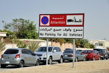 No parking sign, with English and Arabic text  With parked cars  photo