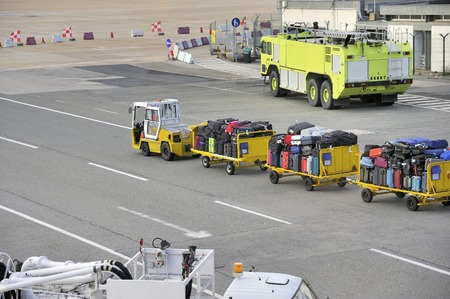 transported: Platform at airport with fire engine and luggage of passengers that is transported by a small trailer