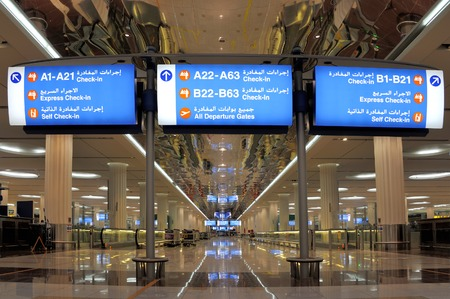 architectural feature: Dubai, United Arab Emirates - February 10, 2014 English Arabic Airport Signs showing the directions of gates and and self check-in at the Dubai International Airport
